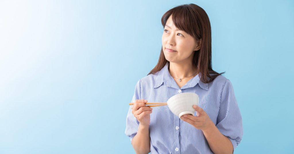 Closeup of woman holding a bowl and chopsticks looking pensive.