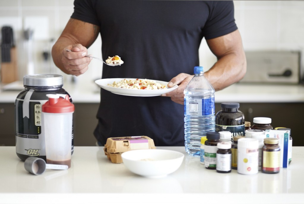 A muscular man holding a bowl of muesli standing in front of his supplements