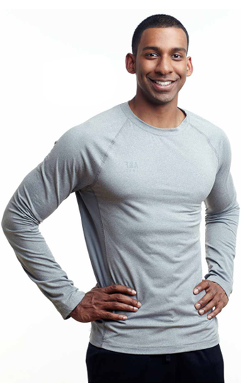Male nutrition coach smiling with hands on hips.