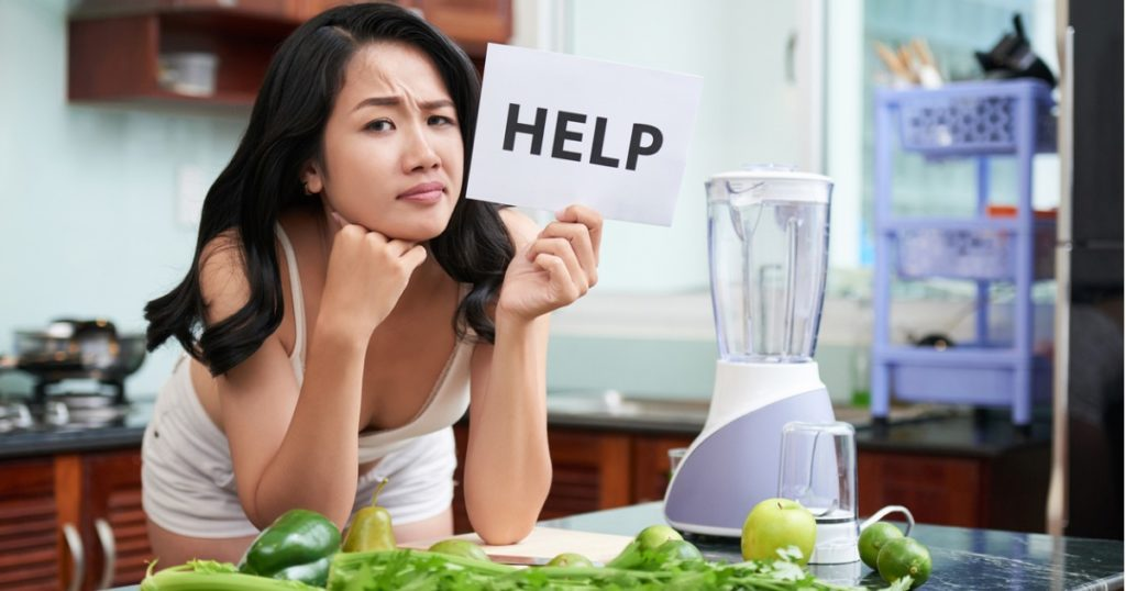 Woman leaning against kitchen counter with fruits and vegetables spread across, holding a white sign that says help.