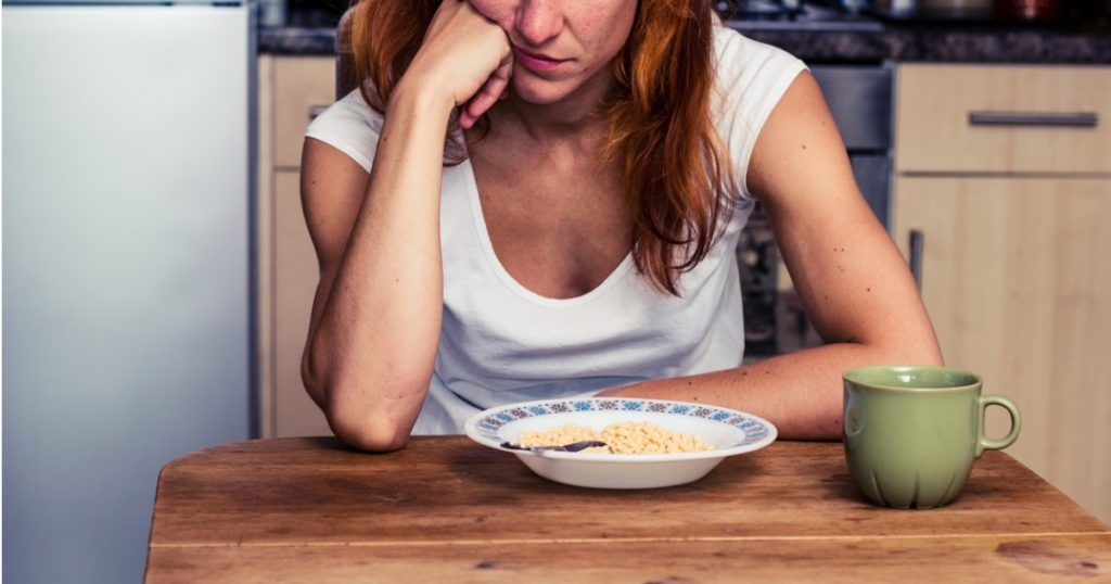 Closeup of woman sitting at the kitchen table, resting her cheek against a closed fist, staring at a bowl of cereal and a coffee mug.