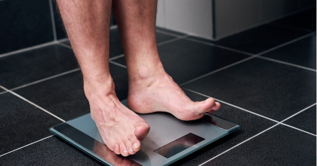 Close-up of bare feet standing on a bathroom scale.