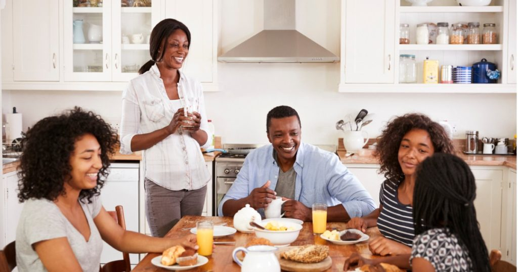 Mother, father and three teenage daughters laughing at the kitchen table over breakfast.