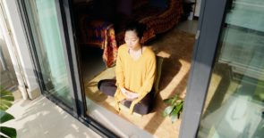 Young asian female sitting cross-legged on the floor in front of an open sliding glass door.