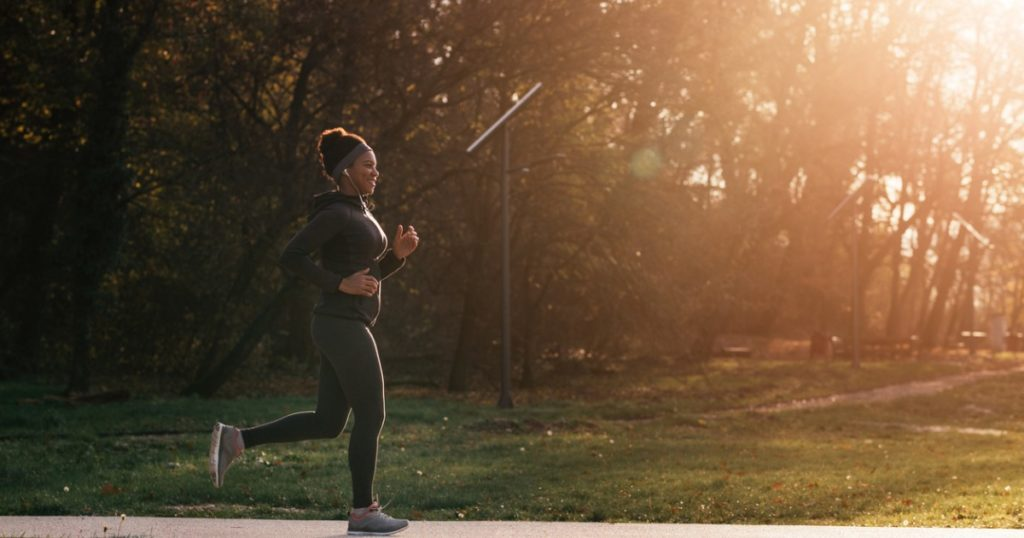 Woman running along a path in a park at sunset.