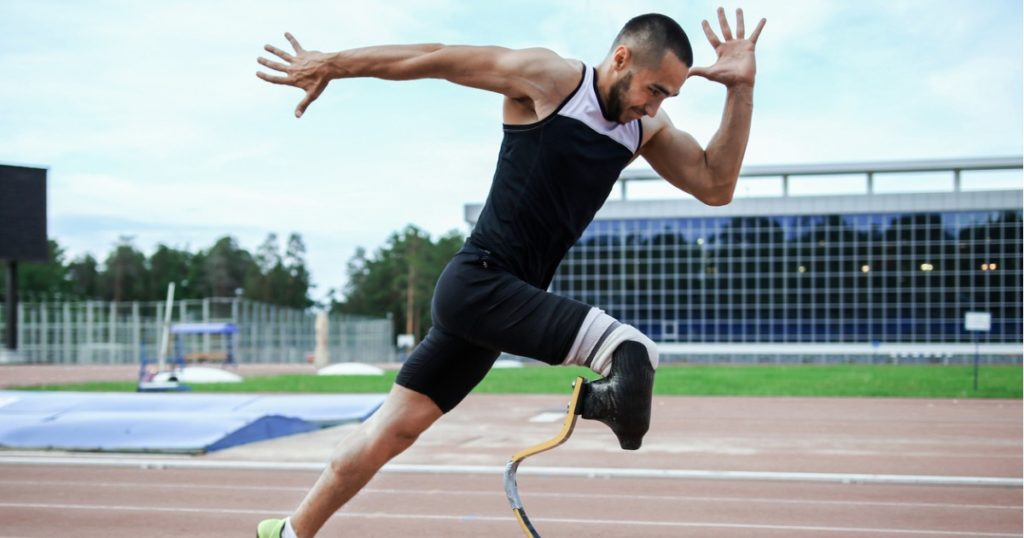 Male athlete with a prosthetic leg in an explosive running position on an outdoor running track.