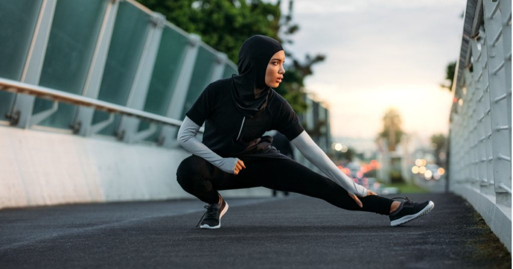 Woman wearing a hijab doing stretches on walkway bridge in the early morning.